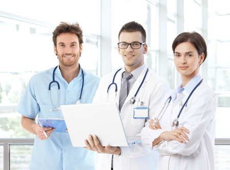 hospital corridor: Portrait of smiling young doctors on hospital corridor looking at camera.� Stock Photo