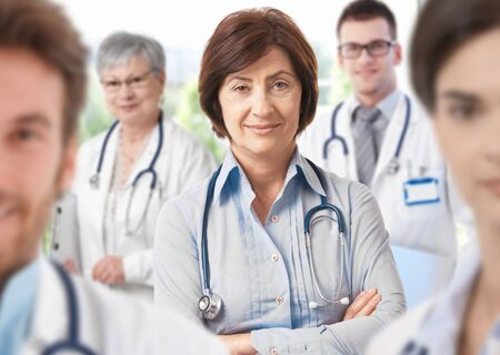 Portrait of middle aged female doctor surrounded by medical team, looking at camera, smiling.� Stock Photo - 9654878