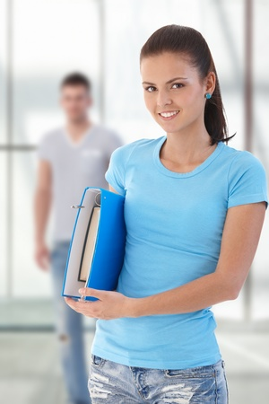 age 16 17 years: Female student holding folder, looking at camera, friend in background.�