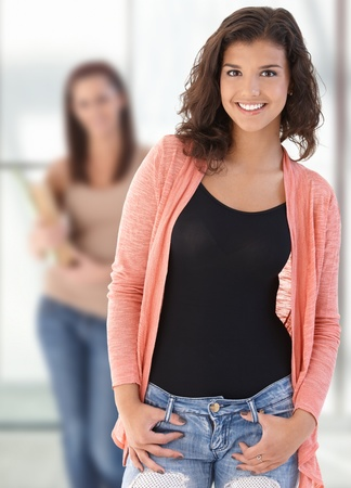 Happy female highschool student looking at camera on school corridor, smiling.� photo