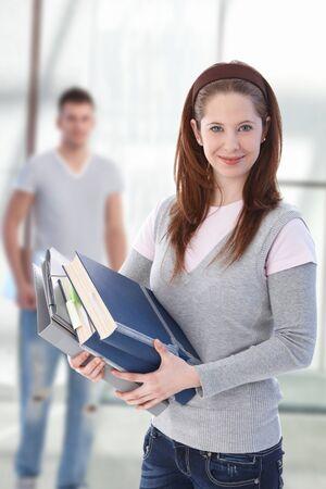 Estudiante de escuela secundaria femenina feliz celebración libros mirando la cámara en el corredor de la escuela, smiling.?