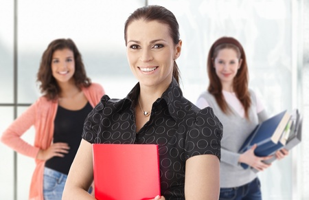 Portrait of smiling female teacher with happy students in background.� photo
