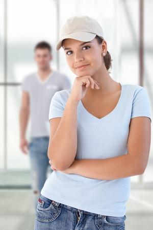 Attractive teenage student in baseball cap standing on school corridor with friends in background.� Stock Photo - 9654883