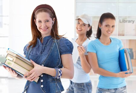 Happy female student holding book in library lobby looking at camera friends in background.� photo