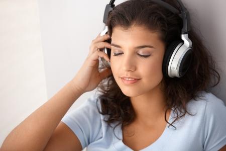 Attractive schoolgirl listening music through headphones, eyes closed. photo