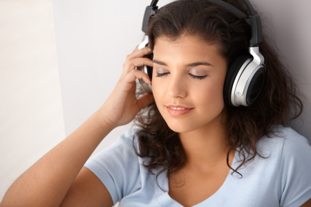 seventeen: Attractive schoolgirl listening music through headphones, eyes closed.