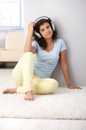 Attractive young woman listening music through headphones, sitting on floor, smiling. Stock Photo - 9712315