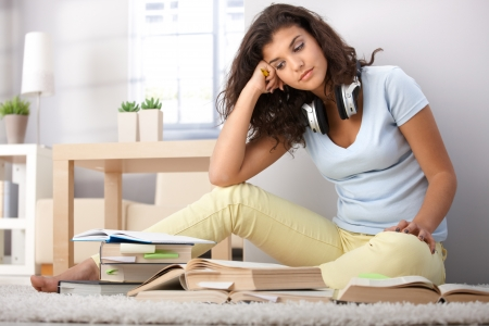 College student sitting on floor, learning at home. Stock Photo - 9712405