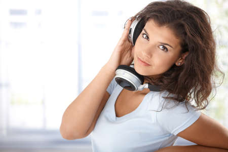 Young woman listening music through headphones, looking at camera, smiling. photo
