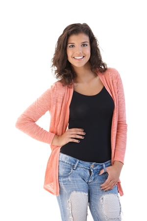 teenagers only: Pretty young girl standing, posing, smiling, looking at camera.