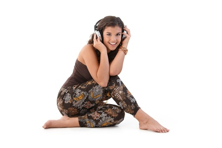 Young woman listening music through headphones, sitting on floor, smiling. photo