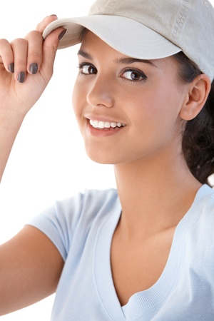 Portrait of attractive young girl in baseball cap, smiling at camera. photo