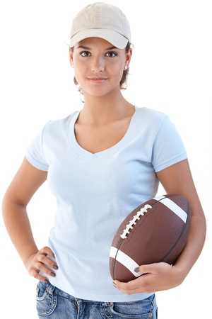Attractive girl holding American football, looking at camera. Stock Photo - 9712697