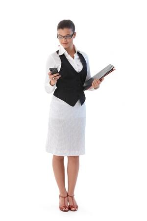 Pretty secretary holding folders, using mobile phone.