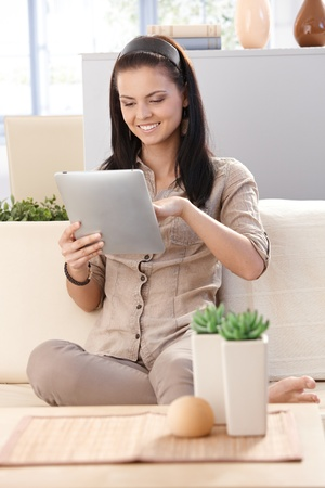 Pretty girl using tablet at home, smiling, sitting on sofa. Stock Photo - 9712728