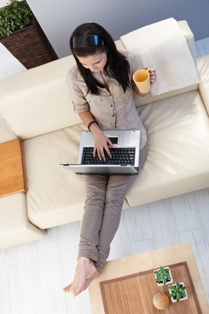 Young woman using laptop at home, sitting on sofa. View from above. photo
