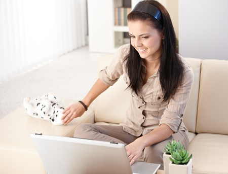 Pretty girl using laptop at home, sitting on sofa, smiling. photo