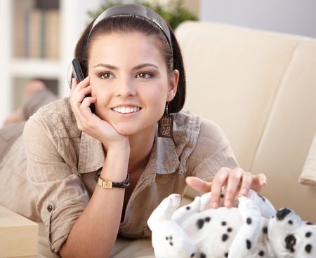 Happy young woman talking on mobile phone, laying on sofa, caressing porcelain dog. photo