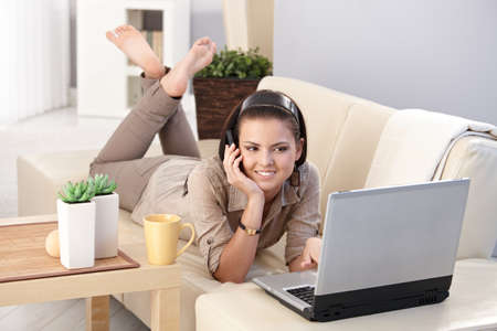 Smiling girl chatting on mobile phone, using computer, laying on sofa, smiling. Stock Photo - 9712314
