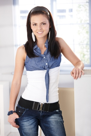 Pretty girl standing at home in jeans and blouse, smiling, looking at camera. photo