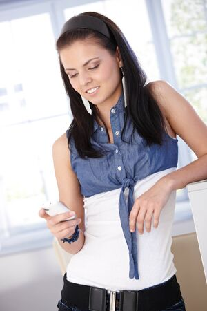 Young female using mobile phone at home, smiling. Stock Photo - 9712722