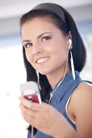 Happy young woman listening music through headset on mobile. photo