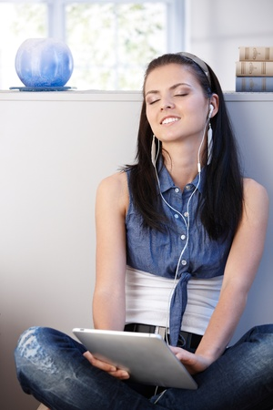 Pretty girl enjoying music through headset and tablet, eyes closed smiling. Stock Photo - 9714123