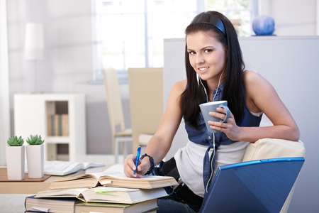 Pretty student learning at home, smiling, looking at camera. Stock Photo - 9712310