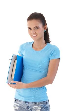 ponytail: Schoolgirl holding folder, smiling, looking at camera.