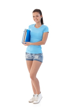Pretty schoolgirl wearing shorts and t-shirt, smiling, holding folder. Stock Photo - 9712062