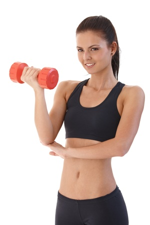 Pretty girl training with dumbbell, smiling, looking away. photo