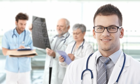 Portrait of young doctor looking at camera, smiling, medical team working in background.� photo