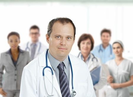 personal medico: Seguro medio a�os masculino doctor mirando a c�mara, sonriente, equipo m�dico en background.? Foto de archivo