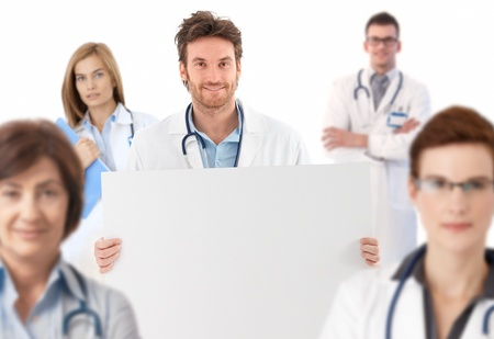 Young male doctor standing in middle of medical team holding blank sheet, white background.� photo
