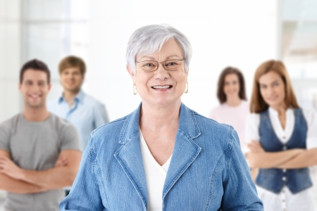 Happy senior teacher looking at camera smiling students in background.� photo