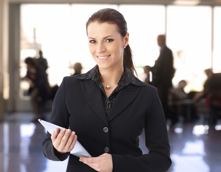 Portrait of businesswoman standing in lobby using tablet computer, looking at camera, smiling. photo