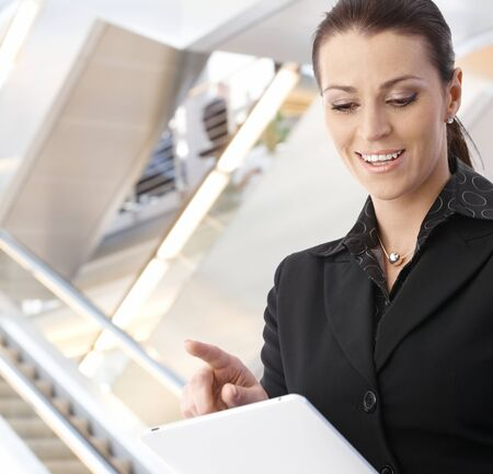 Businesswoman using tablet computer in office building, looking down, smiling. photo