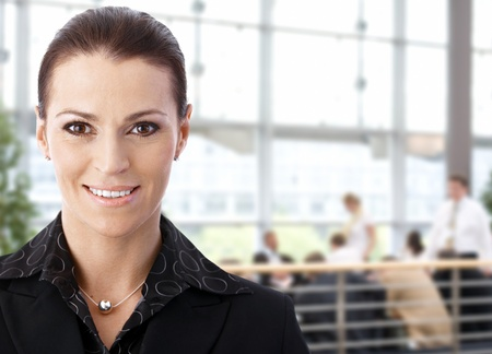 Portrait of happy businesswoman in business lobby, looking at camera, smiling. Stock Photo - 9758494