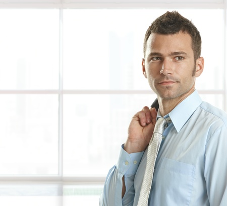 look right: Portrait of confident young businessman looking away, smiling, copyspace on left, Stock Photo