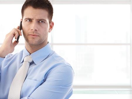 persona llamando: Retrato de joven empresario dedicado mirando a otro lado, hablando por tel�fono m�vil, copyspace a la derecha,