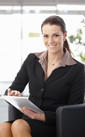Businesswoman sitting in armchair at office using tablet computer, looking at camera, smiling. photo