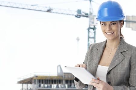 Retrato del arquitecto femenina feliz permanente en sitio de construcción con tablet PC, mirando la cámara, sonriendo.