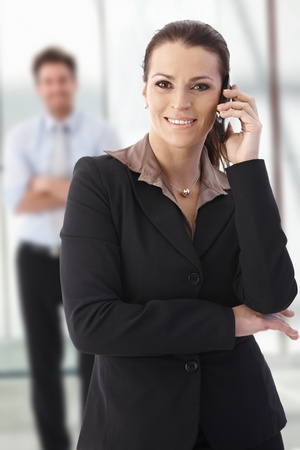 Young businesswoman standing on office corridor, calling, looking at camera, smiling. Stock Photo - 9758498