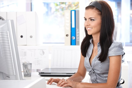 Young office worker sitting at desk, working with computer, smiling. photo