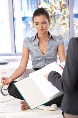 Attractive young office worker meditating in office, boss asking about tasks. photo