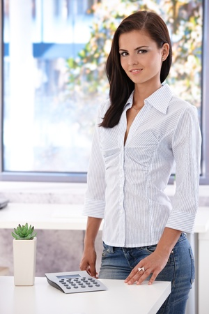 Pretty casual office worker smiling in bright office, standing by desk. photo