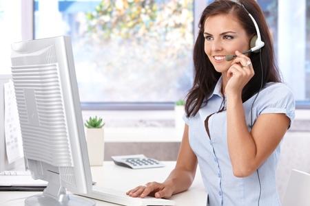 poner atencion: Linda dispatcher trabaja en la Oficina, sonriendo, mirando la pantalla. Foto de archivo