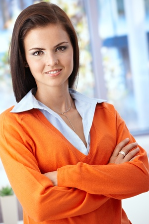 arms crossed: Pretty young woman smiling arms crossed front of window. Stock Photo