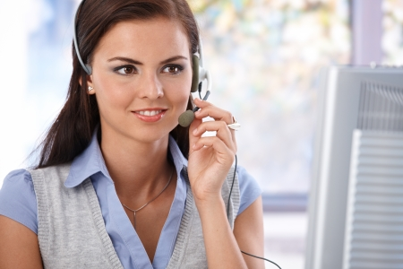customer service representative: Portrait of pretty dispatcher working in bright office, looking at screen. Stock Photo