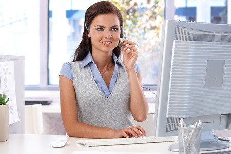 Young customer service operator working in bright office, sitting at desk, smiling.